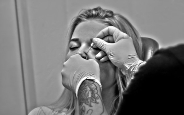 Nose piercing being performed